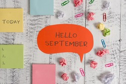 Word writing text Hello September. Business concept for Eagerly wanting a warm welcome to the month of September Blank speech bubble paper balls clips sticky notes old wooden background.