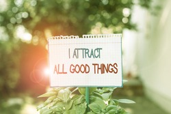 Word writing text I Attract All Good Things. Business concept for Positive attraction law Motivation Affirmation Plain empty paper attached to a stick and placed in the green leafy plants.
