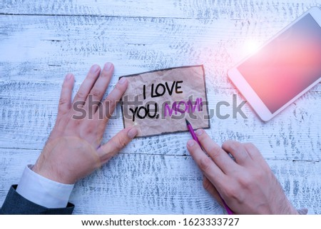 Word writing text I Love You, Mom. Business concept for Loving message emotional feelings affection warm declaration Hand hold note paper near writing equipment and modern smartphone device.
