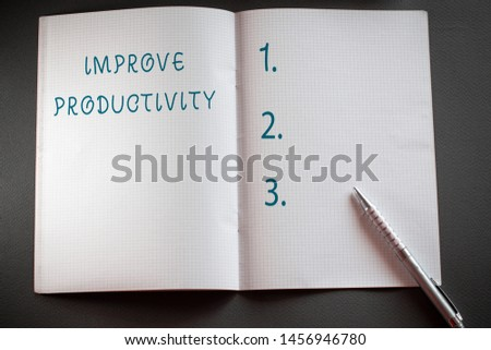 Word writing text Improve Productivity. Business concept for to increase the machine and process efficiency Checkered math book and classic silver pen placed above textured work desk.
