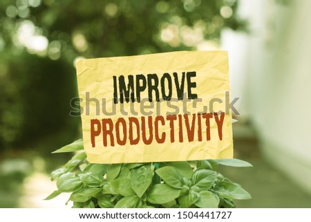 Word writing text Improve Productivity. Business concept for to increase the machine and process efficiency Plain empty paper attached to a stick and placed in the green leafy plants.