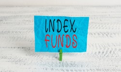 Word writing text Index Funds. Business concept for mutual fund built to match the stocks of a market index Green clothespin white wood background colored paper reminder office supply.