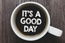 Word writing text It s is A Good Day. Business concept for Happy time great vibes perfect to enjoy life beautiful Black coffee with coffee mug floating texts on gray black wooden desk.