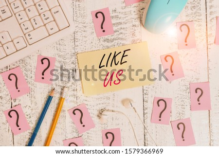 Word writing text Like Us. Business concept for Asking to follow on social media Feel attraction or pleasure Writing tools, computer stuff and scribbled paper on top of wooden table. #1579366969