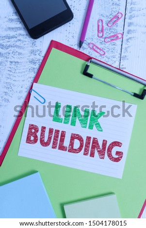 Word writing text Link Building. Business concept for SEO Term Exchange Links Acquire Hyperlinks Indexed Clipboard sheet pencil smartphone note clips notepads wooden background.