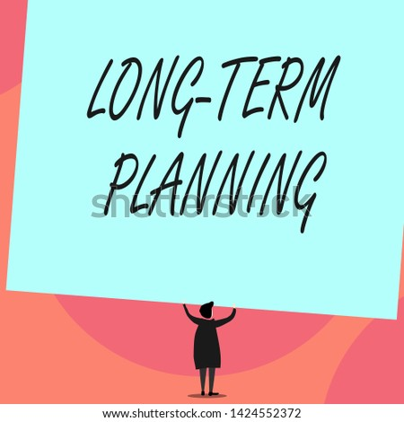 Word writing text Long Term Planning. Business concept for Establish Expected Goals five or more years ahead Back view standing short hair woman dress hands up holding blank rectangle.