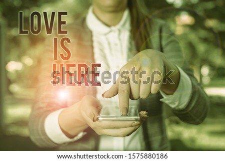 Word writing text Love Is Here. Business concept for Roanalysistic feeling Lovely emotion Positive Expression Care Joy Woman in grey suites holds mobile phone. #1575880186