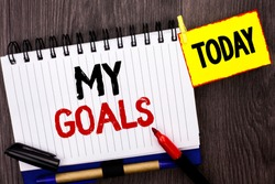 Word writing text My Goals. Business concept for Goal Aim Strategy Determination Career Plan Objective Target Vision written on Notebook Book on the wooden background Today Marker next to it.