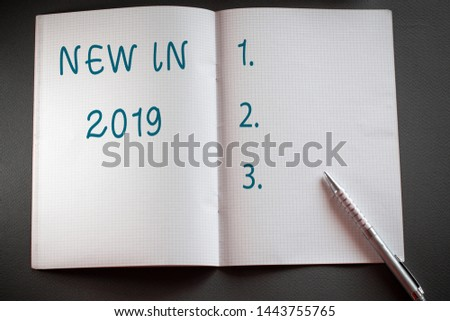 Word writing text New In 2019. Business concept for what will be expecting or new creation for the year 2019 Checkered math book and classic silver pen placed above textured work desk. #1443755765