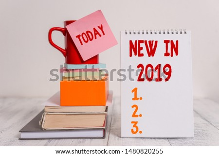 Word writing text New In 2019. Business concept for what will be expecting or new creation for the year 2019 Cup sticky note stacked note pads books square box spiral wooden table. #1480820255