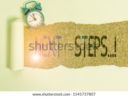 Word writing text Next Steps. Business concept for something you do after you have finished doing first one Alarm clock and torn cardboard placed above a wooden classic table backdrop. #1545737807