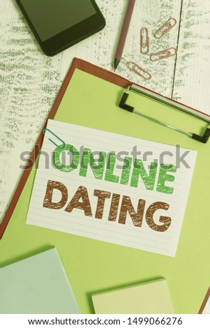 Word writing text Online Dating. Business concept for Searching Matching Relationships eDating Video Chatting Clipboard sheet pencil smartphone note clips notepads wooden background.