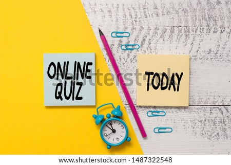 Word writing text Online Quiz. Business concept for game or a mind sport that are published on the Internet Notepads marker pen colored paper sheet alarm clock wooden background.