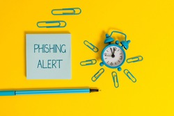 Word writing text Phishing Alert. Business concept for aware to fraudulent attempt to obtain sensitive information Metal alarm clock wakeup clips ballpoint notepad colored background.