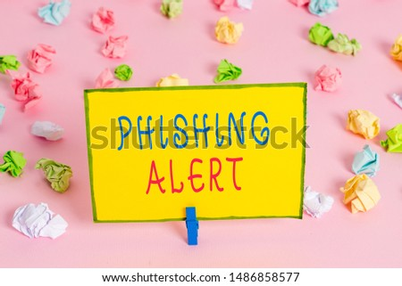 Word writing text Phishing Alert. Business concept for aware to fraudulent attempt to obtain sensitive information Colored crumpled papers empty reminder pink floor background clothespin.