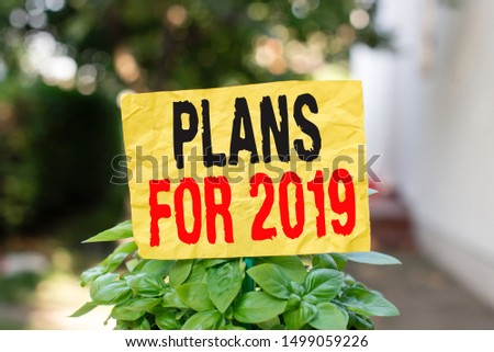 Word writing text Plans For 2019. Business concept for an intention or decision about what one is going to do Plain empty paper attached to a stick and placed in the green leafy plants. #1499059226