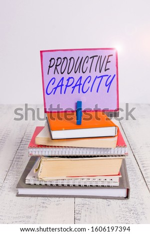 Word writing text Productive Capacity. Business concept for the maximum possible output of a production plant pile stacked books notebook pin clothespin colored reminder white wooden.