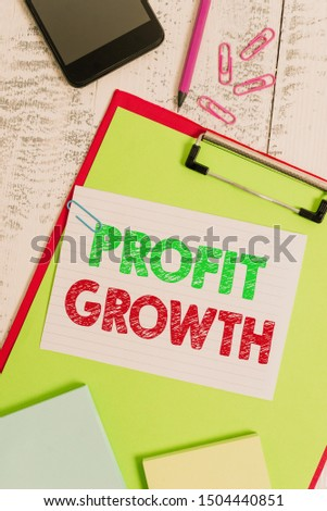 Word writing text Profit Growth. Business concept for Objectives Interrelation of Overall Sales Market Shares Clipboard sheet pencil smartphone note clips notepads wooden background.