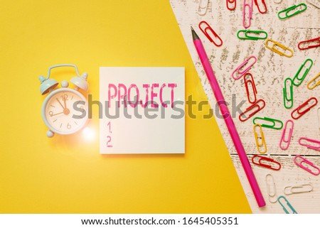 Word writing text Project. Business concept for Planned work activity Study of particular subject Creative job Notepad marker pen colored paper sheet clips alarm clock wooden background.