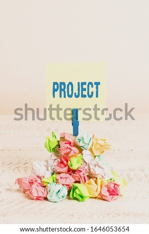 Word writing text Project. Business concept for Planned work activity Study of particular subject Creative job Reminder pile colored crumpled paper clothespin reminder white wooden space.