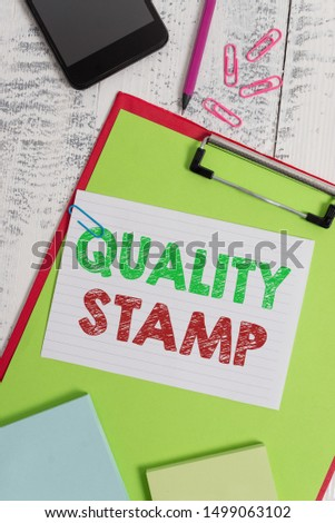 Word writing text Quality Stamp. Business concept for Seal of Approval Good Impression Qualified Passed Inspection Clipboard sheet pencil smartphone note clips notepads wooden background.