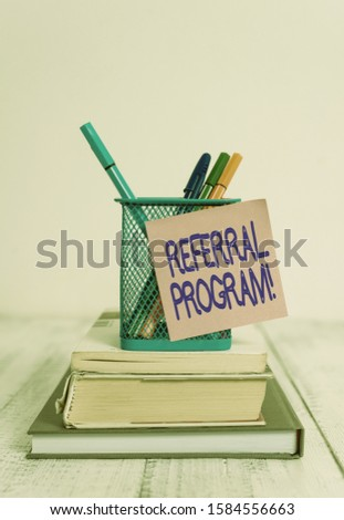 Word writing text Referral Program. Business concept for internal recruitment method employed by organizations Stacked books pens metal holder sticky note lying vintage old wooden table.