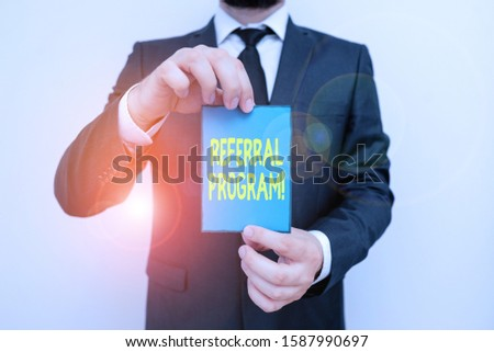Word writing text Referral Program. Business concept for internal recruitment method employed by organizations Male human wear formal work suit office look hold notepaper sheet use hand.
