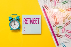 Word writing text Retweet. Business concept for in twitter repost or forward a message posted by another user Notepad marker pen colored paper sheet clips alarm clock wooden background.