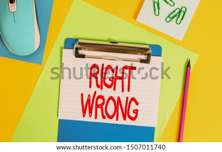 Word writing text Right Wrong. Business concept for choose between two decisions correct and bad one to make Clipboard striped sheets marker clips notepad mouse colored background.
