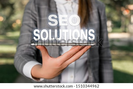 Word writing text Seo Solutions. Business concept for Search Engine Result Page Increase Visitors by Rankings Outdoor scene with business woman holds lap top with touch screen. #1510344962
