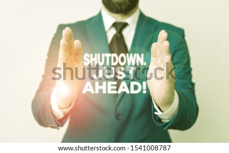 Word writing text Shutdown Just Ahead. Business concept for closing factory business either short time or forever Man with opened hands in fron of the table. Mobile phone and notes on the table. Stockfoto ©