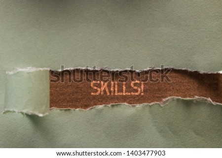 Word writing text Skills. Business concept for ability do something very well by nature Long hole sheet blank paper wrapped paper tear. Wooden table background. #1403477903