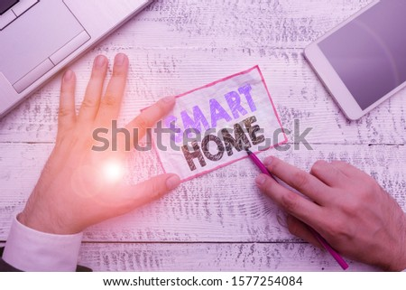 Word writing text Smart Home. Business concept for automation system control lighting climate entertainment systems Hand hold note paper near writing equipment and modern smartphone device. #1577254084