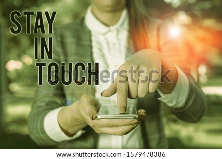 Word writing text Stay In Touch. Business concept for Keep Connected thru Phone Letters Visit Email Social Media Woman in grey suites holds mobile phone. #1579478386