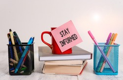 Word writing text Stay Informed. Business concept for having a lot of knowledge or information about something Coffee cup blank sticky note stacked books pen metal holders wooden table.