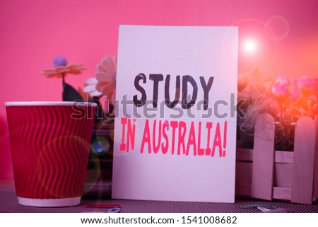 Word writing text Study In Australia. Business concept for going into foreign country order complete your studies Flowers and stationary plus plain sheet with paper big cup above a table.