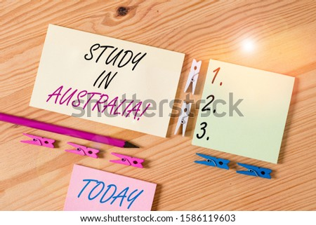 Word writing text Study In Australia. Business concept for going into foreign country order complete your studies Colored clothespin papers empty reminder wooden floor background office.