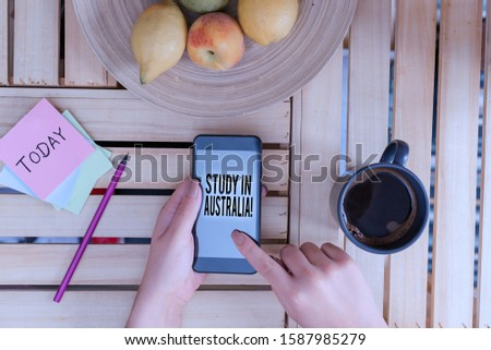Word writing text Study In Australia. Business concept for going into foreign country order complete your studies woman computer smartphone drink mug office supplies technological devices.