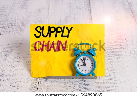 Word writing text Supply Chain. Business concept for network between a company and suppliers in producing a product Mini blue alarm clock stand tilted above buffer wire in front of notepaper. #1564890865