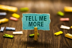 Word writing text Tell Me More. Business concept for A call to start a conversation Sharing more knowledge Clothespin holding blue paper note reminder clothespins wooden floor.