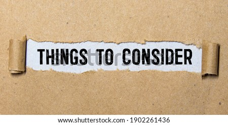 Word writing text Things To Consider. Business concept for think about something carefully in order to make decision Cardboard which is torn in the middle placed above a wooden classic table. ストックフォト ©