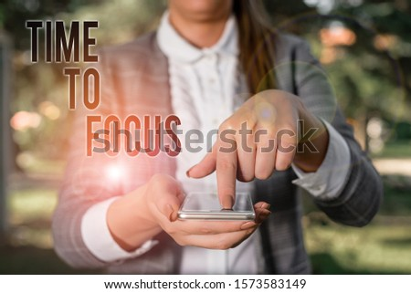 Word writing text Time To Focus. Business concept for Give full attention to something or activity Key to success Woman in grey suites holds mobile phone. #1573583149