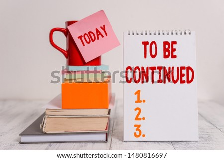 Word writing text To Be Continued. Business concept for indicate that the story continues in the next episode Cup sticky note stacked note pads books square box spiral wooden table. #1480816697