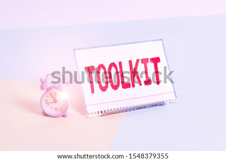 Word writing text Toolkit. Business concept for set of tools kept in a bag or box and used for a particular purpose Mini size alarm clock beside a Paper sheet placed tilted on pastel backdrop. #1548379355