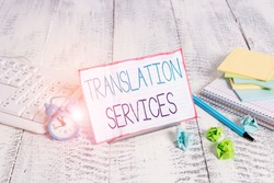 Word writing text Translation Services. Business concept for organization that provide showing to translate speech Notepaper stand on buffer wire in between computer keyboard and math sheets.