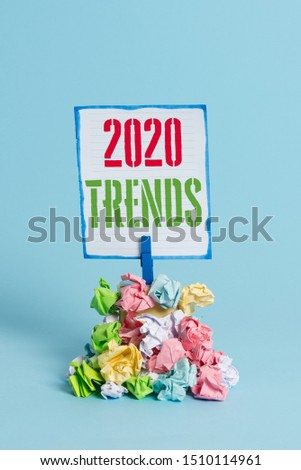 Word writing text 2020 Trends. Business concept for things that is famous for short period of time in current year Reminder pile colored crumpled paper clothespin reminder blue background.