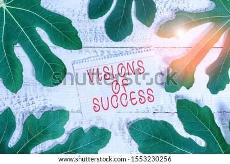 Word writing text Visions Of Success. Business concept for Clear End Result of Purpose Goal Perspective Plan Leaves surrounding notepaper above a classic wooden table as the background.