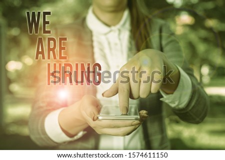 Word writing text We Are Hiring. Business concept for Workforce Wanted HR recruiting new hire employee Vacancy Woman in grey suites holds mobile phone. #1574611150