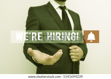 Word writing text We Re Hiring. Business concept for recently employ someone or pay him to do particular job Male human with beard wear formal working suit clothes raising one hand up.