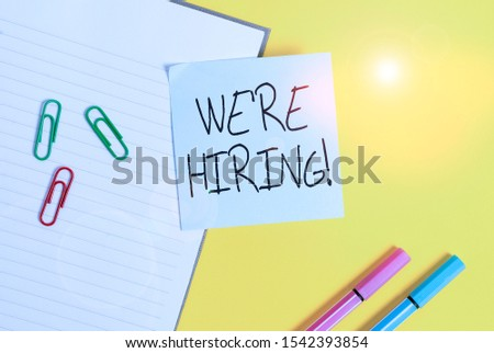 Word writing text We Re Hiring. Business concept for recently employ someone or pay him to do particular job Empty blue paper with copy space paper clips and pencils on the yellow table.